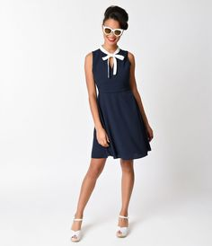 Retro, refined and radiant! A criminally classy dress with stylish navy pinstripes and a darling white self tie bow on front that creates a sultry keyhole. The breezy and lightweight chiffon crepe is lined with soft poly knit, side darts flatter your form