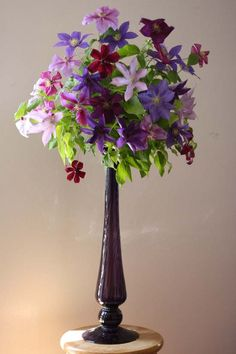 Alicia of Bella Fiori's Design. Purple vase filled with a variety of Clematis flowers.
