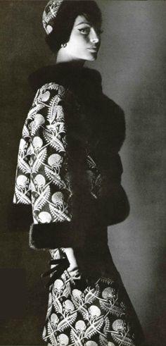 1961 Christian Dior. Col et bordure de vison noir sur ce tailleur noir et or, en lamé à gros motifs en relief. Veste courte et assez ample. Sous la veste se cache le corsage de la robe fourreau. La jupe est un peu clochée.