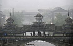 Ethnic Dong minority villagers walk through a covered bridge on their way to a Kam Grand Choir gathering in Tongguan village of Liping county, Guizhou province, on October 17, 2011