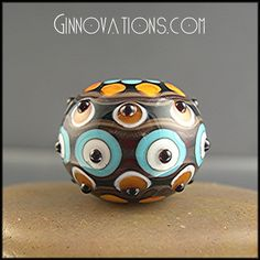 a richly colorful and highly detailed focal bead (created by me!) using Italian Effetre and CIM glass in jet black, khaki beige, deep transparent amber, mango coral, bright turquoise, a touch of light ivory, and a bit of glittering goldstone. This piece was created on a base of black which was decorated with many layers of precisely placed lines and dots and is accented with 3 rows of little raised black bumps.
