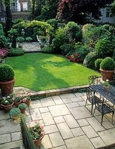 Small formal town garden with paved patio, dining table and chairs, lawn, containers, borders and arch dividing separate patio at far end of garden – London A bit formal for my taste, but like the use of space.