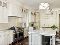 A pair of Grosvenor Single Pendants illuminate a gray kitchen island topped with a white and grey ...