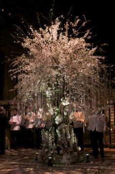 Escort Card Tree created from hundreds of stems of White Cherry Blossom branches sitting on a base on Hybrid White Delphinium, Hydrangea and White Macarena Roses.