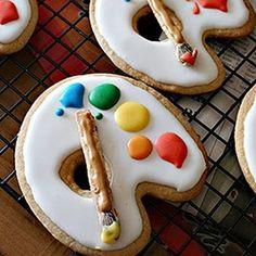 Sugar cookies with icing, pretzel sticks, and raisin 'brush'