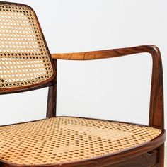 A close up of a vintage 'Oscar' Armchair by Sergio Rodrigues in solid Jacaranda wood with back and seat in cane. The stunning pair of these chairs is on display at our NY showroom.