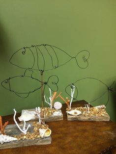 Fish made of wire mounted on reclaimed wood and decorated with pebbles, shells and branches made to look like corral.