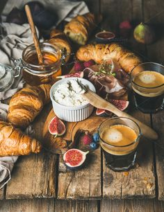 #Breakfast with croissants  Breakfast with croissants ricotta cheese figs fresh berries prosciutto meat honey in glass jar and two glasses of espresso coffee over rustic wooden background selective focus