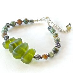 """Olivine: Green Handmade Beaded Bracelet  This beaded bracelet of olivine tumbled sea glass and semi-precious unakite will pair beautifully with autumnal earth tones. Closes at 7"""" with a 1"""" extender."""