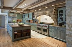 What an amazing kitchen- natural beams, Stonework, Blue antiqued cabinetry, wood and stone flooring- all awesome