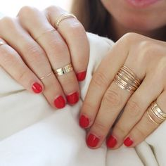 { red nails with gold stacking rings }