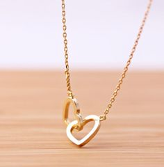 """crossed heart necklace, """"never gets apart"""""""