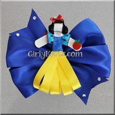 Sosteniendo la manzana roja, esta bella princesa lleva su satinado vestido de amarillo y azul real con un pequeño lazo rojo en su cabello. Ella mide