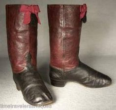"""1865 young boy's fancy two tone leather boots with tall oxblood colored Moroccan leather tops and black leather whole vamps. Decorated at the top with matching silk gros grain ribbon bows and black silk tassels. Kid leather linings that are each penned """"10"""", leather foot beds, and striped ticking boot pulls shown here in and out. . 1"""" stacked leather heels, and rounded square toes. 7"""" from heel to toe, 2 1/4"""" wide and 9 1/4"""" tall outside measure."""