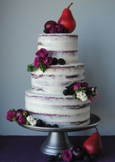 Semi naked red velvet wedding cake with cream cheese frosting. Decorated with deep pink spray roses and autumnal fruit. Great for a fall wedding, from the Handmade Cake Company