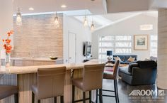 Accented by a stunningly large skylight, the focal point of this kitchen is the dramatic counter to ceiling stone backsplash that matches the warm wood cabinetry and floors. Stainless steel appliances and chef's sink provide a modern contrast to the natural elements and pull-out storage provides easy access to frequently used items. The under cabinet wine fridge and custom stainless steel and glass hood add extra personalized touches to this very distinct kitchen.