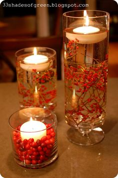 Use fresh berries (these are rose hips) to decorate the length of an apothecary jar then float a candle.  #centerpiece #fall