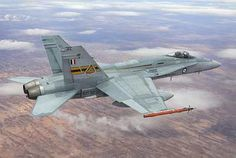 An RAAF F/A-18A Hornet, from the Aircraft Research and Development Unit, carries a pair of JDAM-ER guided weapons on the way to Woomera Test Range.