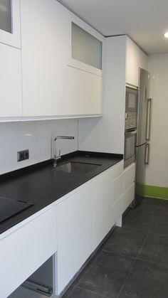 El color mate de los muebles de cocina contrasta con la superficie brillante del gres de las paredes, mientras que la encimera y suelo ambos de material porcelánico de tonos grafito dialogan entre sí.