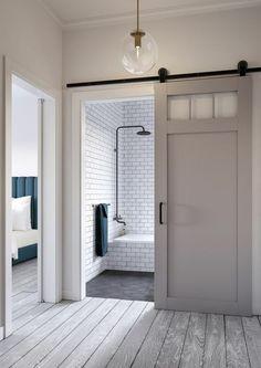 porte de grange coulissante modernisée, rail coulissant en acier noir, salle de bains en briques