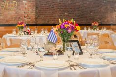Ballard Bay Club North Room: The tables are decorated with colorful flowers and travel themed decor! #Brick #SeattleWedding