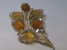 1960's Gold Tone Butterscotch Molded Glass Floral Brooch with enameled long leaves an aurora borealis rhinestone at the end of each molded glass blossom.  The stones alternate in a pale butterscotch to a honey colored flower. It has a textured undercarriage typical of 1960's.  It is not signed.