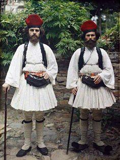 """Σερδαρέοι: Χωροφύλακες στις Καρυές του Αγίου Όρους 1913, Stéphane Passet.""""Διορίζονται υπό της Ιεράς Επιστασίας, τη προτάσει των Ιερών Μονών, εν αις προϋπηρέτησαν ως δασοφύλακες, υποχρεούμενοι άμα τη κατατάξει αυτών να φέρωσιν ευπρεπή ενδυμασίαν μετά πολυπτύχου φουστανέλλας, μετά ερυθρού καλύμματος της κεφαλής μεγάλου, όπερ αποκλίνει προς τα οπίσω μετά θυσσάνου, και περιδέδεται κύκλω δια ταινίας μελαίνης πλάτους δύο δακτύλων ως έγγιστα προς ένδειξιν της παρά τη Ιερά Κοινότητι υπηρεσίας αυτών"""" Mykonos, Greek Independence, Albert Kahn, Greek Isles, Royal Guard, Robert Doisneau, Old Photos, Greece, Folk"""