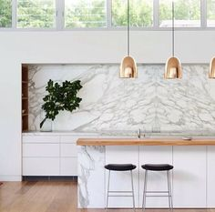 Modern White Calcutta marble kitchen accented with hints of copper