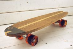 """Skateboard. Old skool design. Named """"Nieuwe Haring"""". To be used as a mini cruiser. With a nice fish tail. The name """"Nieuwe Haring"""" (new herring) is derived from a typical Dutch treat. Fresh young herring fish, eaten raw in spring. A typical Dutch tradition.   Deck: combination of oak- and esh wood. Finished with transparent varnish. Limited editions. Length: 25"""". Width: 5.9"""". Thick: 0.59"""". Trucks (3""""), wheels (red, blue or white transparent) and bearings by Penny."""