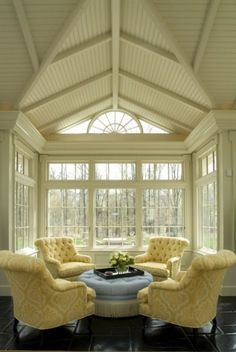 Tufted traditional chairs in buttercream yellow are a pretty touch in this spectacular living space.