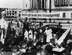 """The Nazi """"Winter Relief Organization"""" serving food adjacent to the Kaiser-Wilhelm Memorial Church, 1930's. The banner reads """"Today Berlin eats its one-pot meal."""""""