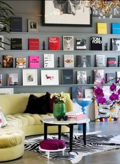 colorful wall of books. I love so much about this room!!!  The book display, a tufted sofa, gray walls!  Wow