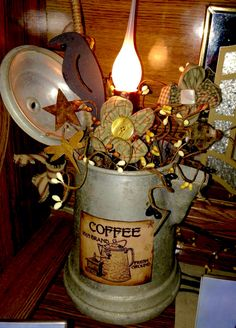Old coffee pot I decorated, made flowers with buttons in the middle, rusty dragonfly, rusty lady bug , black crow and some pip berries. With a coffee label glued on the front.  Made by Cindys primitives.