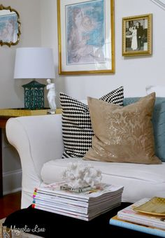 Glam living room mini-makeover with black, white, coral pink, teal blue, and gold.  Throw pillows and inexpensive accessories add visual interest.