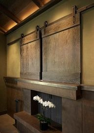 "barn doors cover tv. Protects for flying objects, Im sure kids will play ballin the house sometime. Id love to have a fireplace under it. Maybe thats what that is behind the flowers?? :))"" data-componentType=""MODAL_PIN"