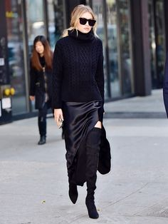 Gigi Hadid wears a chunky turtleneck sweater with a satin slit skirt and thigh-high suede boots.