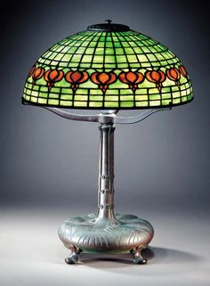 A 'POMEGRANATE' LEADED GLASS AND BRONZE TABLE LAMP Tiffany Studios, circa 1910 22in. (55.9cm.) high, 15¾in. (40cm.) diameter of the shade, with finial the shade tag stamped TIFFANY STUDIOS NEW YORK, the base stamped TIFFANY STUDIOS NEW YORK 9518