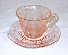 These are Depression Glass cup and saucer sets in the Royal Lace pattern made by Hazel Atlas. The color is pink and they are in very nice condition with no chips or cracks.