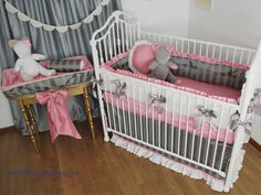 Pink and Grey crib bedding with white silk and a decorative bow in the nursery