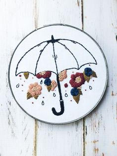 Its raining flowers! (Wouldnt that be amazing?)  These flowing flowers are all hand embroidered with tedious French knot centers and textured leaves.   THIS PIECE ▴ ▴ ▴ ▴ ▴ ▴ ▴ ▴  ▴ Comes in a sturdy 6 vintage metal embroidery hoop. ▴ This umbrella is raining maroon, deep blue and peach flowers.  ▴ Ready to hang and brighten your walls!  *This hoop is made to order. Please allow for slight variances in flower placement, shape etc.*   WHY ITS SPECIAL ▴ ▴ ▴ ▴ ▴ ▴ ▴ ▴▴ ▴ ▴ ▴  ▴ Handmade to the…