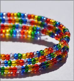 This memory wire bracelet is about three loops wide, depending on wrist size. It features tiny, translucent seed beads in red, orange, yellow, green, blue and purple.    Memory wire is awesome because:  1) It is incredibly sturdy and durable. It can take much more abuse than your average bracelet.  2) It doesn't unclasp or fall off, making it harder to lose!  3) The bendy nature of the wire makes it easily fit larger wrists.  4) It is very easy to put on and take off, none of that annoying clasp nonsense!    $13.00