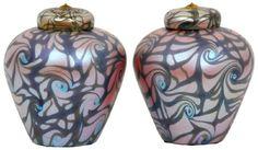 Dois vasos de vidro soprado, cobertos com urnas como tampas, com uma botão aplicado. Têm uma forma de balaústre, com cor alaranjada e decoração verde, iridescente no geral. Arte do rei Tut, assanado por Durand, 1964-10.