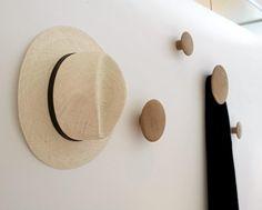 Runde treknagger i ulike størrelser er plassert vilkårlig på veggen. Dette skaper en morsom effekt.