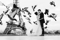 Black and white photo of a newly wed couple kissing between flying pigeons in front of the Eiffel Tower.  #kissmeinparis #kissinparis #blackandwhitephotos #paris #eiffeltower #wedding #bride #groom #romantic #weddinginspiration