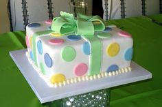 Gender neutral baby shower cake. Pastel polka dots with a green bow.