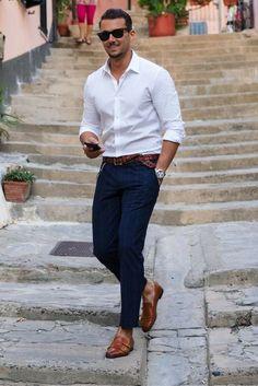 El está llevando una camisa blanco y unos pantalones azul. El está llevando unos zapatos. Los zapatos cuesta sesenta euros. La camisa cuesta cincuenta euros. Los pantalones cuesta sesenta euros.