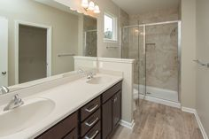 Master bathroom features luxury vinyl tile (LVT) floors, marbelite counters, stained cabinetry, a ceramic tile shower surround, and a glass shower door.