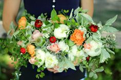 Late May bridal bouquet full of white peonies, blush garden roses, peach ranunculus, red ranunculus, and lots of seasonal foliage. Grown and designed by Love 'n Fresh Flowers in Philadelphia.