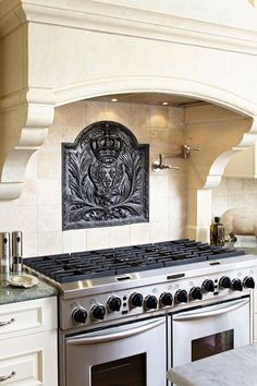 A French inspired kitchen with a stately limestone range hood and an 18th century French iron fireback.