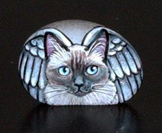 rock I had painted in honor of my Kitty Grey who lived with me 21 yrs. there were a lot of rock painters on E Bay in 2009, but not many now. I have the rocks in my memorial garden.